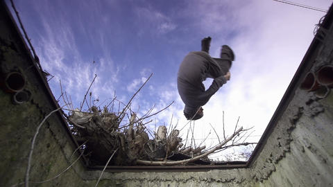 SLOW MOTION: Free runner does side flip over a man Footage