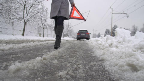 Woman placing warning triangle on the road Live Action