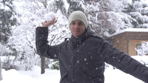 SLOW MOTION: Young man throwing a snowball Footage