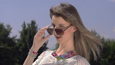 SLOW MOTION: Beautiful woman takes off her sunglas Footage