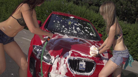 SLOW MOTION: Girls in bikinis washing a car Footage