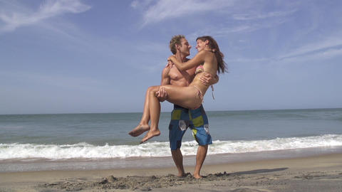 SLOW MOTION: Man carrying and spinning his girlfri Footage