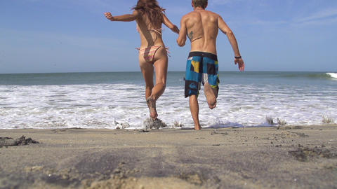 SLOW MOTION: Young couple running into the sea Footage