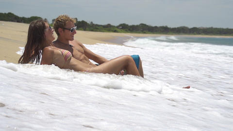 SLOW MOTION: Young couple lying on the shore Footage