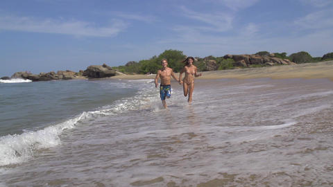 SLOW MOTION: Young couple running in shallow water Footage