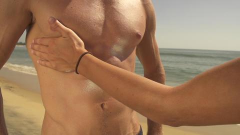Female applying sun screen on her boyfriend's body Footage