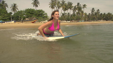 Female surfer jumps on the surfboard and starts pa Footage