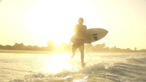 SLOW MOTION: Surfer goes surfing at sunset Footage