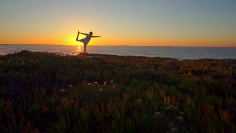 AERIAL: Woman doing yoga by the ocean Footage