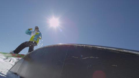 SLOW MOTION: Snowboarder rides a rainbow box Footage