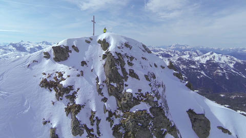 AERIAL: Backcountry skier standing on top of the m Footage
