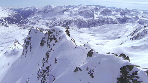 AERIAL: Flying above the snowy mountain ridge Footage