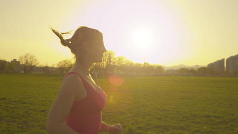 SLOW MOTION: Young woman jogs at sunset Footage