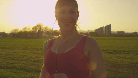 SLOW MOTION: Cheerful female jogger running toward Footage