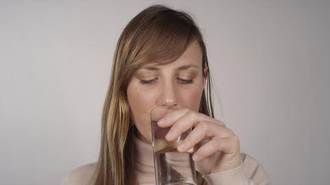 Young woman takes a pill and drinks water Footage