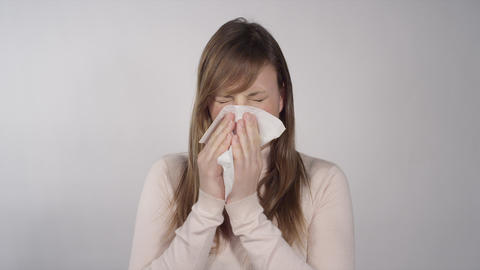 Ill woman blowing her nose with a tissue Live Action