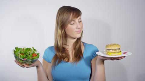 Woman Choosing Between Fast And Healthy Food stock footage