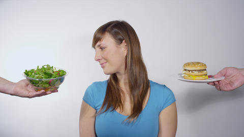 Woman Choosing Between Healthy And Unhealthy Eatin stock footage