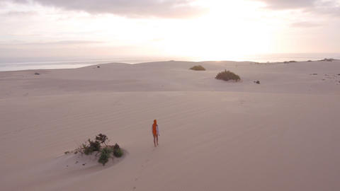 AERIAL: Woman walking through desert towards the o Footage