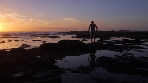 AERIAL: Man Walking Into The Ocean At Sunrise stock footage
