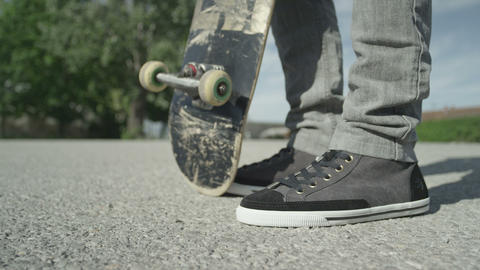 SLOW MOTION CLOSE UP: Skateboarder Picking Up His  stock footage