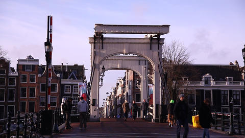 People and cyclists pass on Skinny Bridge Amsterda Footage