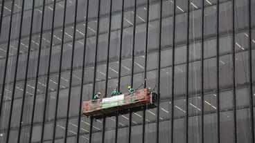 Workers Clean And Seal Glass Windows Of Highrise B stock footage