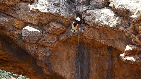 Female rock climber slides on rope in a sunny summ Footage