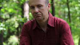 Sad, Pensive Man Sitting In The Forest 3 stock footage