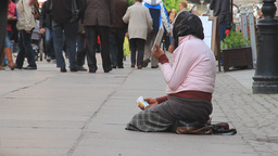 Old, poor woman is begging for money on the street Footage