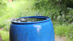 Rain water fills blue water barrel during a rain Stock Video Footage