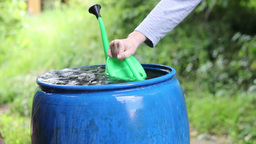 Woman takes rainwater from a blue barrel Stock Video Footage