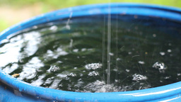Rain water fills blue water barrel during a rain Footage