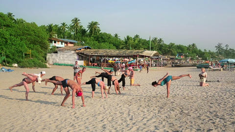 GOA, INDIA - MARCH 2013: People practicing yoga on Footage
