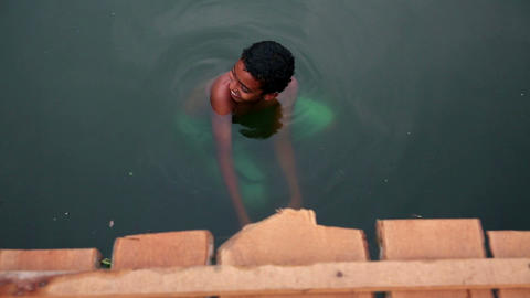 ALLEPPEY, INDIA - MARCH 2013: Boy bathing in canal Footage
