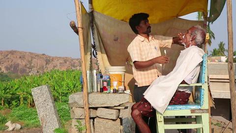 HAMPI, INDIA - APRIL 2013: Local barber at work Stock Video Footage