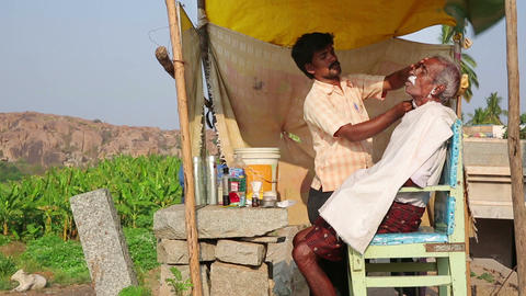 HAMPI, INDIA - APRIL 2013: Local barber at work Footage