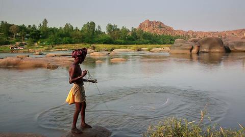 HAMPI, INDIA - APRIL 2013: Fisherman casting nets Stock Video Footage