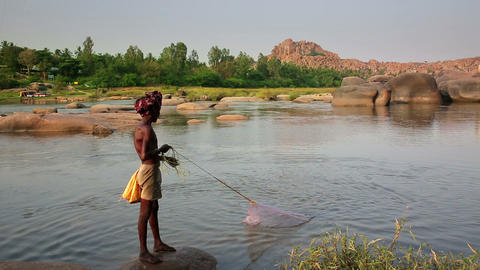 HAMPI, INDIA - APRIL 2013: Fisherman casting nets Footage