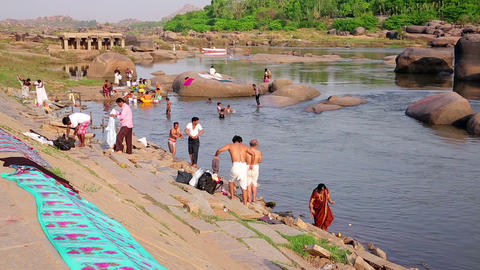 HAMPI, INDIA - APRIL 2013: People bathing in river Stock Video Footage