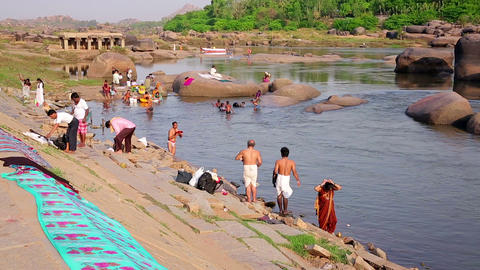 HAMPI, INDIA - APRIL 2013: People bathing in river Footage