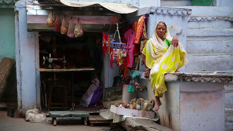 UDAIPUR, INDIA - APRIL, 2013: Woman sitting outsid Stock Video Footage