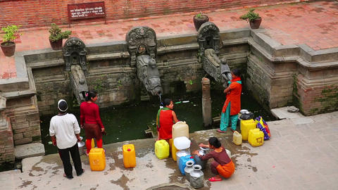KATHMANDU, NEPAL - JUNE 2013: people pouring water Footage
