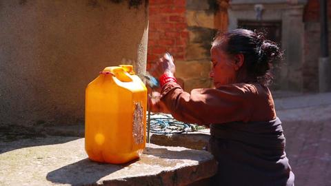 KATHMANDU, NEPAL - JUNE 2013: old woman pulling wa Stock Video Footage