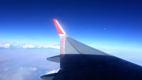 Airplane wing out of window on blue sky background Footage