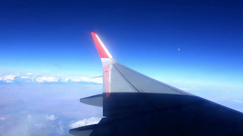 Airplane wing out of window on blue sky background Stock Video Footage