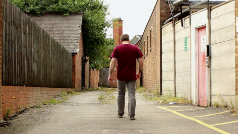 Guy walks narrow alley - montage Filmmaterial
