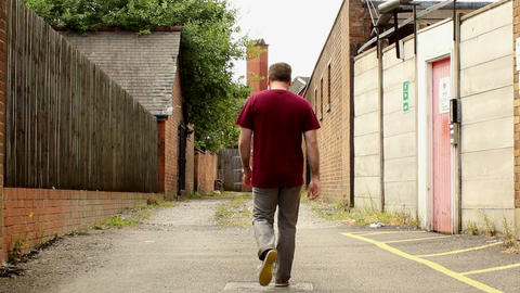 Guy walks narrow alley Footage