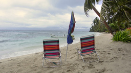 Chairs And Umbrella On A Tropical Beach Shoreline stock footage