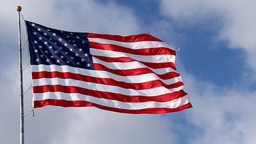 American Flag Waving Against Blue Sky stock footage